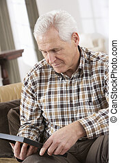 Sad Senior Man Looking At Photograph In Frame
