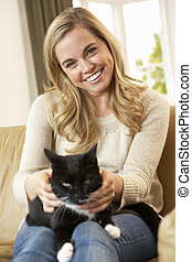 Happy young woman with cat sitting on sofa