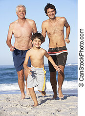 Grandfather, Father and Grandson Running Along Beach