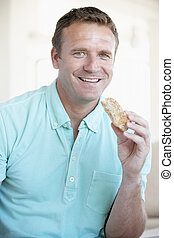 Mid Adult Man Eating Brown Bread Roll