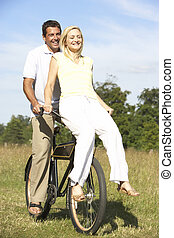 Young couple riding bike in countryside