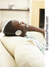 Young Man Relaxing Sitting On Sofa Listening to Music At...