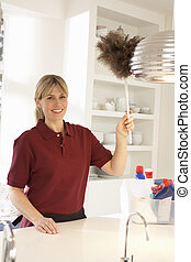 Cleaner Working In Domestic Kitchen With Feather Duster