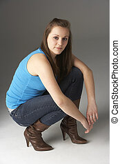 Teenage Girl Kneeling In Studio