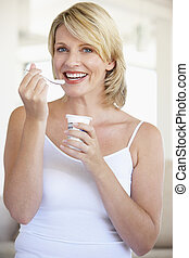 Mid Adult Woman Eating Yogurt