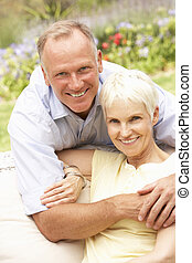 Senior Woman And Adult Son Relaxing In Garden