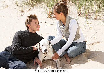 Portrait Of Romantic Teenage Couple On Beach With Dog