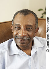 Senior Man Relaxing In Chair At Home