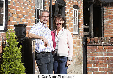 Farmer And Wife Standing In Front Of Farmhouse