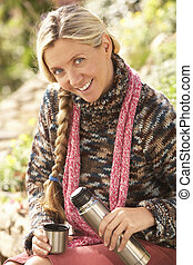 Young Woman Relaxing With Thermos Flask In Autumn Landscape