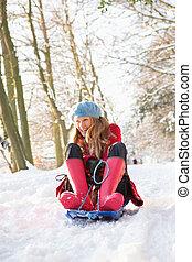 Woman Sledging Through Snowy Woodland