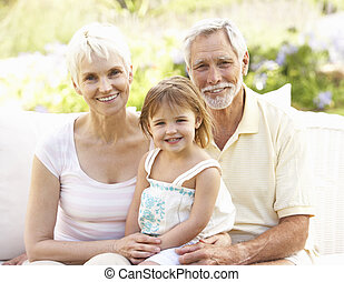Grandparents And Granddaughter Relaxing In Garden