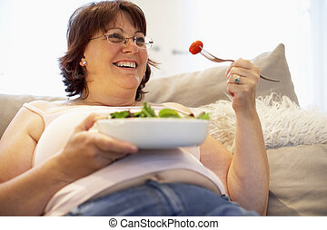 Overweight Woman Relaxing On Sofa