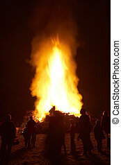 People Standing Around A Big Bonfire At Night