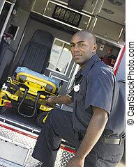 Paramedic removing empty gurney from ambulance