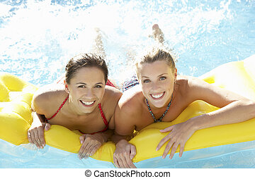 Two women friends having fun together in pool