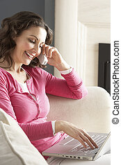Woman Using Laptop Relaxing Sitting On Sofa At Home Talking...