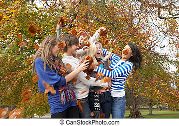 Group Of Teenage Friends Throwing Leaves In Autumn Landscape