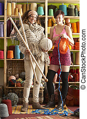 2 Women Wearing Knitted Scarf Standing In Front Of Yarn...