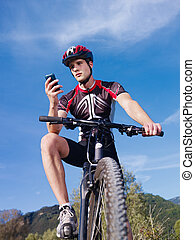 young man with telephone riding mountain bike - sports...