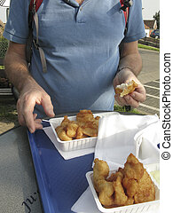 Eating fried fish outdoors - Man taking a piece of fried...