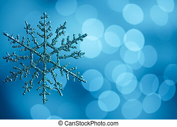 snowflake against blue bokeh lights background with copy...
