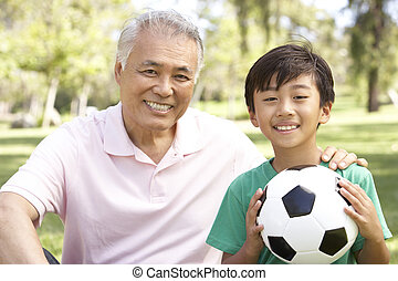 Grandfather And grandson In Park With Football