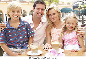 Young Family Enjoying Cup Of Coffee In Caf? Together