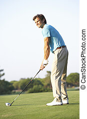 Male Golfer Teeing Off On Golf Course