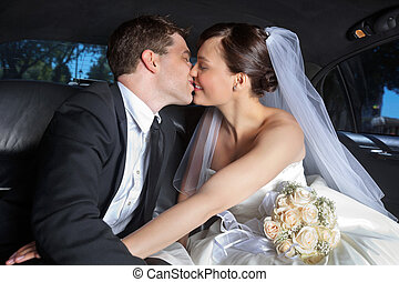 Wedding Couple Kiss in Limo - Newlywed couple kissing each...