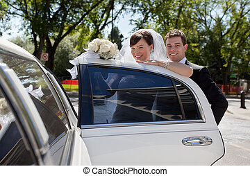 Bridge and Groom entering Limo - Happy wedding couple...