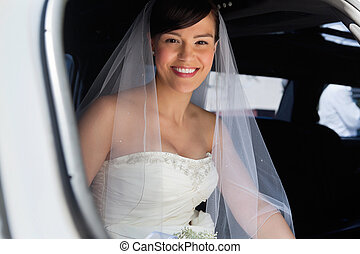 Happy Bride in Limo - Attractive bride sitting in car and...