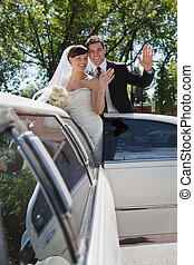 Wedding Couple Waving - Bride and groom standing in Limo...