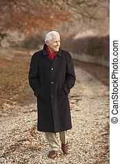 Senior Man On Winter Walk Through Frosty Landscape