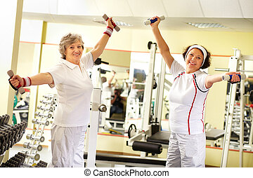 Seniors weightlifting - Two pretty senior women exercising...
