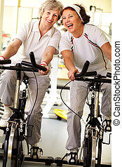 Seniors exercising - Portrait of two cheerful grandmas...