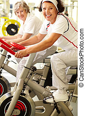 Sport for seniors - Two positive senior women exercising in...