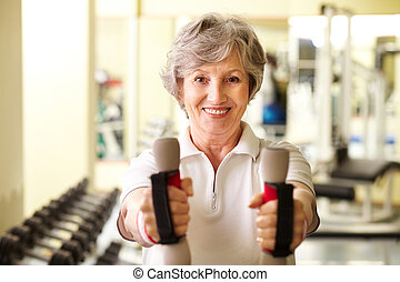 Training with dumbbells - Portrait of pretty senior woman...