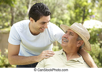 Senior Man With Adult Son In Garden