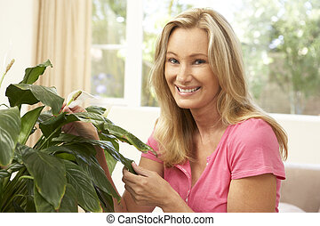 Woman At Home Looking After Houseplant