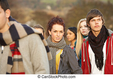 Teenage Girl Surrounded By Friends In Outdoor Autumn Landscape