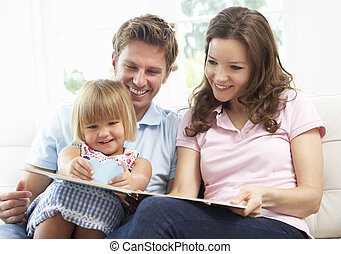 Family Sitting On Sofa Reading Book At Home