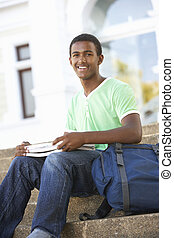 Male Teenage Student Sitting Outside On College Steps