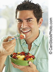 Mid Adult Man Holding A Bowl Of Fresh Fruit Salad Smiling At The Camera