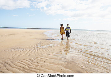 Romantic Young Couple Walking Along Shoreline Of Beach...