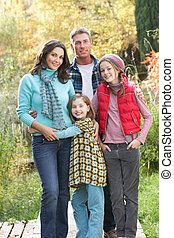Family Group Standing Outdoors On Wooden Walkway In Autumn...