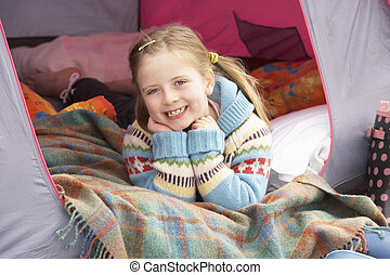 Young Girl Relaxing Inside Tent On Camping Holiday