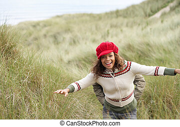 Teenage Girl Walking Through Sand Dunes Wearing Warm...