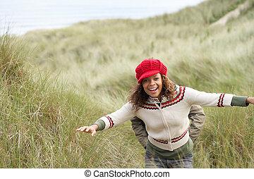 Teenage Girl Walking Through Sand Dunes Wearing Warm...