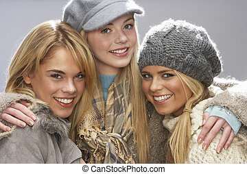Three Fashionable Teenage Girls Wearing Cap And Knitwear In...